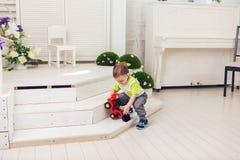 El niño pequeño está jugando con el coche del juguete en casa fotografía de archivo