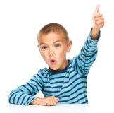 El niño pequeño está mostrando el pulgar encima de la muestra Imagen de archivo libre de regalías