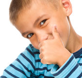 El niño pequeño está mostrando el pulgar encima de la muestra Fotografía de archivo