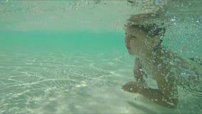 El niño pequeño está nadando debajo del agua metrajes