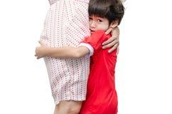 El niño pequeño está ocultando a su madre con asustadizo Fotos de archivo