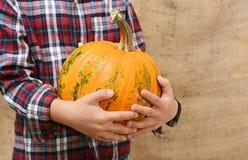 El niño pequeño está sosteniendo una calabaza anaranjada grande Foto de archivo