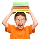 El niño pequeño está sosteniendo una pila de libros Fotos de archivo libres de regalías