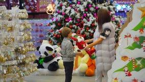 El niño pequeño está trayendo dos juguetes de Santa Claus a su madre elegir Ubicación del centro comercial almacen de metraje de vídeo