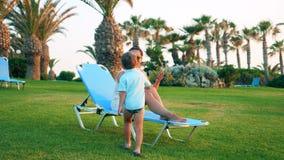 El niño pequeño está viniendo a una señora que se relaja en una cubierta-silla almacen de video