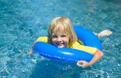 El niño pequeño feliz con el anillo de vida azul se divierte en el po que nada Foto de archivo libre de regalías