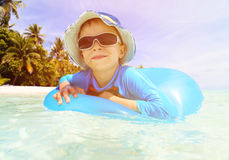 El niño pequeño feliz con el anillo de vida se divierte en la playa Imagenes de archivo