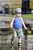 El niño pequeño feliz en chaleco y pantalones cortos camina en un charco Imagenes de archivo