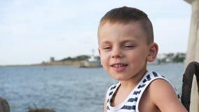 El niño pequeño feliz en marinero raya la camisa en fondo del cielo y del mar almacen de video