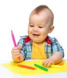 El niño pequeño feliz está jugando con las etiquetas de plástico coloridas Foto de archivo libre de regalías