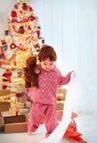 El niño pequeño feliz lindo en pijamas tiene su presente en la Navidad Foto de archivo libre de regalías