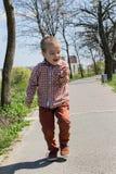 El niño pequeño feliz sostiene una hormiga en su mano fotos de archivo