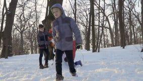 El niño pequeño fresco acabado haciendo el muñeco de nieve y va lejos de muchachos en la cámara lenta almacen de metraje de vídeo