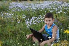 El niño pequeño goza de un ordenador portátil en la naturaleza Imagenes de archivo