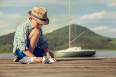 El niño pequeño hace los barcos de papel que se sientan en el embarcadero de madera Imagenes de archivo