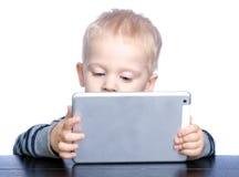 El niño pequeño hermoso con el pelo rubio y los ojos azules está sosteniendo a Fotografía de archivo