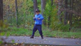 El niño pequeño juega el beyblade del giroscopio del juguete al aire libre en parque del otoño