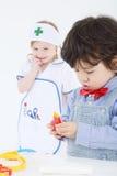 El niño pequeño juega con los instrumentos médicos del juguete y la muchacha mira fotografía de archivo