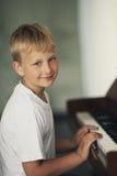 El niño pequeño juega el piano Imagenes de archivo
