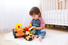 El niño pequeño juega los coches en casa Foto de archivo