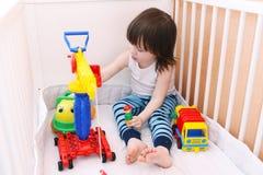 El niño pequeño juega los coches en la cama blanca Foto de archivo