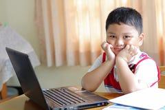 El niño pequeño jugaba el cuaderno. Imagen de archivo