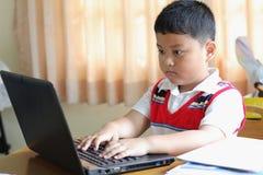 El niño pequeño jugaba el cuaderno. Foto de archivo libre de regalías