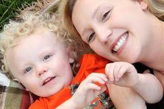 El niño pequeño levemente sonriente abraza al aire libre en la manta con la mamá bonita Imagenes de archivo