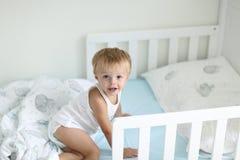 El niño pequeño lindo acaba de despertar el uo a partir del tiempo de la siesta y está sonriendo feliz imagen de archivo