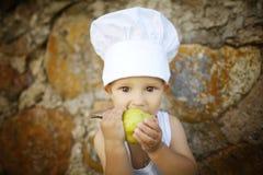 El niño pequeño lindo come la manzana Imágenes de archivo libres de regalías