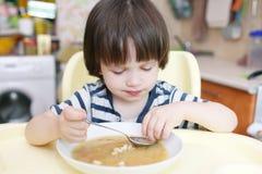 El niño pequeño lindo come la sopa de guisantes Foto de archivo libre de regalías