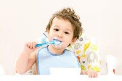El niño pequeño lindo con la cuchara azul es yogur Las sonrisas del niño niño divertido en un asiento del bebé consumición de 2 a fotos de archivo