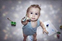 El niño pequeño lindo con el suyo da sucio en las pinturas que muestran su finger en la cámara foto de archivo