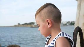 El niño pequeño lindo en marinero raya la camiseta en fondo del cielo y del mar metrajes