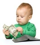 El niño pequeño lindo está contando el dinero Imagen de archivo