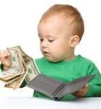 El niño pequeño lindo está contando el dinero Imagenes de archivo