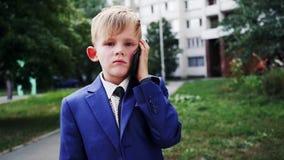 El niño pequeño lindo está hablando por smartphone grande