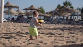El niño pequeño lindo juega con la bola en la playa en la cámara lenta almacen de metraje de vídeo
