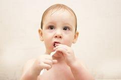 El niño pequeño lindo limpia sus dientes en un baño, y juegos con un cepillo de dientes imagen de archivo