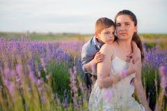El niño pequeño lindo que abraza a la madre bonita entre campos del verano de la lavanda florece en día de oro caliente de la pue Foto de archivo libre de regalías