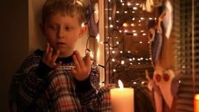 El niño pequeño lindo que se sienta en el alféizar que cuenta permanecer de los días labra la Navidad almacen de metraje de vídeo
