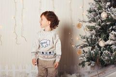 El niño pequeño lindo se está sentando con un regalo cerca del árbol de navidad El niño es feliz con el regalo del Año Nuevo cauc foto de archivo