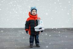 El niño pequeño lindo sostiene los patines que llevan la ropa caliente g del invierno Imagen de archivo libre de regalías