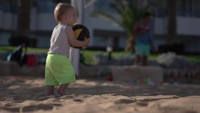 El niño pequeño lindo toma la bola del voleibol en la playa y los paseos en la playa almacen de metraje de vídeo