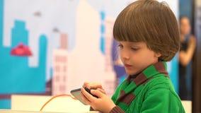 El niño pequeño lindo utiliza un smartphone El robot demostró para los niños en el 4to festival ruso de la ciencia El evento esta metrajes