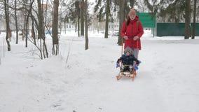 El niño pequeño lindo y la madre joven juegan en el invierno con nieve en el parque Chaqueta azul y rojo del ` s del niño en la m metrajes