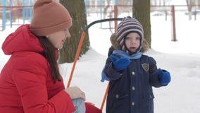 El niño pequeño lindo y la madre joven juegan en el invierno con nieve en el parque Chaqueta azul y rojo del ` s del niño en la m almacen de metraje de vídeo