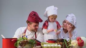 El niño pequeño lindo y sus padres hermosos están sonriendo mientras que cocina en cocina Familia joven que cocina la comida en c almacen de video