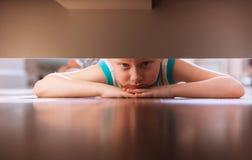 El niño pequeño mira debajo de la cama Imagenes de archivo