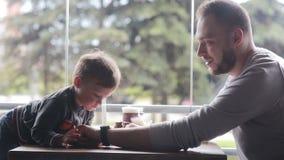 El niño pequeño mira el smartclock en la mano del padre almacen de metraje de vídeo